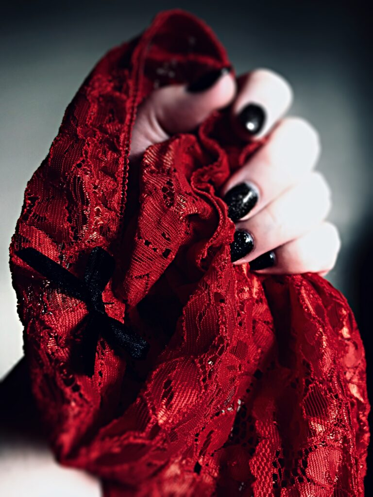 red lace panties clutched in a hand with black glittery nail polish