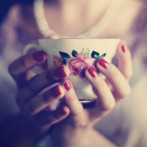 Tea? pretty feminine red nailed hands hold a classic floral teacup