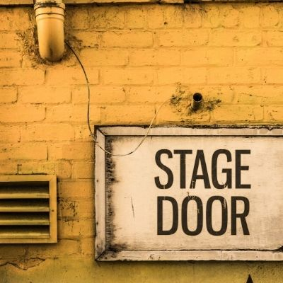 "yellow brick wall with a white sign that reads ""stage door"""